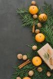 La composición del Año Nuevo de la Navidad con las mandarinas encajona verdes de los conos del pino en la decoración negra del dí Fotografía de archivo