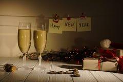 La composición del Año Nuevo de los vidrios de champán, encendiendo las guirnaldas, los presentes y los números de madera mostran Fotografía de archivo