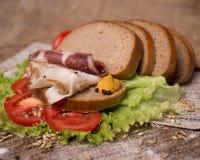 La composición del bocadillo con tocino y el tomate en una ensalada hojean Fotos de archivo