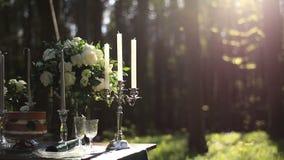 La composición del candelabro blanco del vintage y del ramo de las rosas blancas en la boda adornó la tabla en el bosque romántic almacen de metraje de vídeo