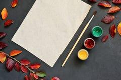 La composición del otoño con el documento, las acuarelas y el cepillo del arte sobre el tablero de tiza, adornó las hojas rojas Imagen de archivo