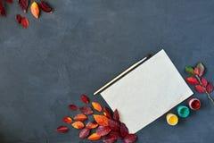 La composición del otoño con el documento, las acuarelas y el cepillo del arte sobre el tablero de tiza, adornó las hojas rojas Foto de archivo