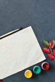 La composición del otoño con el documento, las acuarelas y el cepillo del arte sobre el tablero de tiza, adornó las hojas rojas Imagenes de archivo