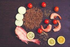 La composición del plato incluye pescados del mero, el limón cortado, cebollas tajadas, el arroz moreno, el camarón y las especia fotos de archivo libres de regalías