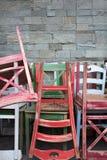 La composición del srt de la calle de las sillas coloridas del vintage colocó cerca de la pared de piedra del café Imágenes de archivo libres de regalías