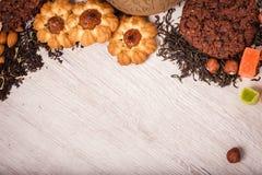 La composición del té en una superficie de madera dispersión del té, de la almendra y de la avellana Té verde, negro Galletas y c imagen de archivo libre de regalías