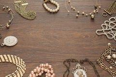 La composición del vintage pone la joyería plana para las mujeres en fondo de madera Imagen de archivo libre de regalías