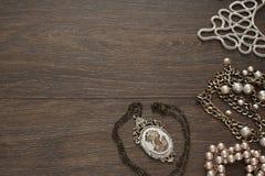 La composición del vintage pone la joyería plana para las mujeres en fondo de madera Foto de archivo