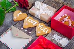 La composición festiva con las galletas hechas en casa en la forma del corazón con te amo poner letras, subió, caja de regalo tar fotos de archivo libres de regalías