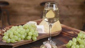 La composición giratoria del queso sirvió con una copa de vino y uvas metrajes
