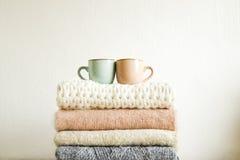 La composición rústica de Minimalistic con el vintage apilado hizo punto los suéteres y la taza de café en el fondo blanco de la  imagenes de archivo
