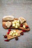 La composition avec du bois olive, olives, pain, fromage rapièce en huile d'olive, épices Images libres de droits