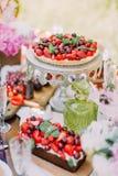 La composition de mariage des gâteaux délicieux de fruit d'éponge décorés des cerises juteuses et des fraises et sont placées des Image stock