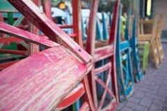 La composition de srt de rue des chaises colorées de vintage a placé près du mur en pierre du café Image libre de droits