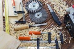 La composition des agrafes, des burins, et des puces sur le bureau dans l'atelier en bois Images libres de droits