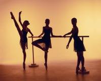 La composition des silhouettes de trois jeunes danseurs dans le ballet pose sur un fond orange Photo libre de droits