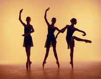 La composition des silhouettes de trois jeunes danseurs dans le ballet pose sur un fond orange Photographie stock libre de droits