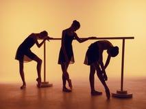 La composition des silhouettes de trois jeunes danseurs dans le ballet pose sur un fond orange Photographie stock