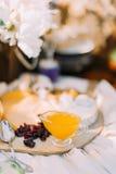 La composition douce du pot de poire entourée par les fruits secs et le fromage situés sur le conseil en bois au brouillé Photo libre de droits