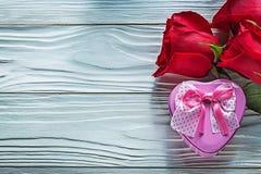 La composition du présent en forme de coeur en métal enferme dans une boîte les roses rouges courtisent dessus Photos libres de droits