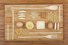 La composition en art avec des pâtes, biscuits, oeufs, cuisine en bois a placé dessus Photos stock