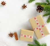 La composition en carte de Noël avec des boîte-cadeau enveloppés en papier d'emballage, sapin s'embranche avec le cône photographie stock libre de droits