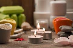La composition en station thermale avec du sel de mer, bougies, savon, écosse, écrème pour le visage sur le fond en bois Photographie stock libre de droits