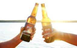 La composition en vacances, se ferment des mains des hommes tenant des bouteilles de bière Groupe de personnes célébrant le Jour  Photo libre de droits