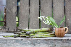 La composition toujours en vie avec l'asperge et le pot en céramique avec le muguet fleurit Images stock