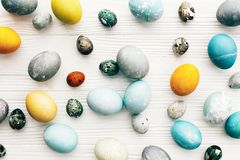 La composizione alla moda nelle uova di Pasqua, mette su pianamente il fondo di legno bianco Uova di Pasqua variopinte moderne di immagini stock libere da diritti