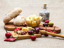 La composizione con legno verde oliva, olive, pane, formaggio collega in olio d'oliva, spezie Immagine Stock