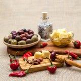 La composizione con legno verde oliva, olive, pane, formaggio collega in olio d'oliva, spezie Fotografie Stock Libere da Diritti