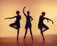 La composizione dalle siluette di tre giovani ballerini nel balletto posa su un fondo arancio Immagine Stock