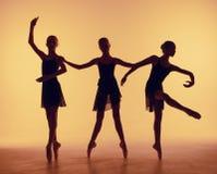 La composizione dalle siluette di tre giovani ballerini nel balletto posa su un fondo arancio fotografie stock