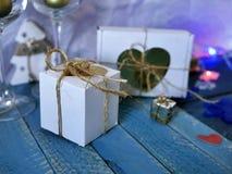 La composizione decorativa di Natale dei regali decorati, luci di Natale, fatte a mano ha ritenuto i cuori, carta su un fondo di  immagine stock