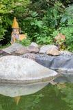 La composizione dei fiori, degli arbusti e del giardino calcola vicino allo stagno Immagine Stock Libera da Diritti