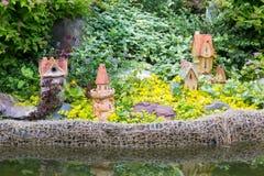 La composizione dei fiori, degli arbusti e del giardino calcola vicino allo stagno Immagine Stock