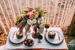 La composizione dei fiori differenti che stanno sulla tavola servita nell'area della festa nuziale Disposizione floreale Fotografia Stock Libera da Diritti