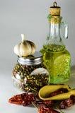 La composizione dei piatti di vetro con l'intero olio di girasole e del pepe ed il peperoncino rosso e l'aglio Immagine Stock Libera da Diritti