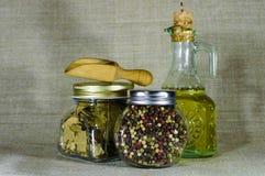 La composizione dei piatti di vetro con le spezie e l'olio di girasole Fotografie Stock
