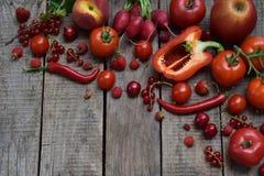 La composizione dei prodotti vegetariani rossi: frutta e verdure su fondo di legno Mele, pomodori, uva passa, ravanelli, pepp Immagini Stock Libere da Diritti