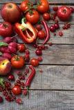 La composizione dei prodotti vegetariani rossi: frutta e verdure su fondo di legno Mele, pomodori, uva passa, ravanelli, pepp Fotografia Stock Libera da Diritti