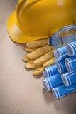 La composizione dei vetri dei guanti della sicurezza del casco della costruzione blueprints Fotografie Stock
