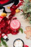 La composizione del nuovo anno alla tavola con la decorazione, la tazza e un orologio rosso fotografia stock libera da diritti