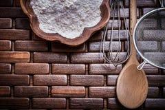 La composizione del setaccio di legno del fiore della ciotola del cucchiaio ed uovo-sbatte Fotografie Stock