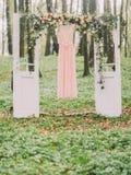 La composizione dell'arco sotto forma di porte bianche decorate con i fiori bianchi e rossi ed il vestito rosa lungo è Immagini Stock Libere da Diritti