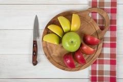 La composizione della mela collega sul tagliere di legno e su un coltello accanto nella vista superiore Immagine Stock Libera da Diritti