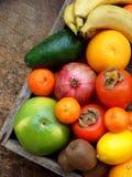 La composizione della miscela ha colorato i frutti tropicali e mediterranei su fondo di legno Concetti circa la decorazione, Fotografia Stock