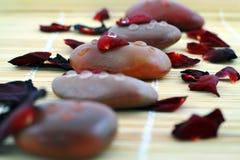 La composizione della stazione termale delle pietre ed i petali rossi di sono aumentato Fotografia Stock