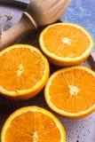 La composizione delle arance fresche mature ha tagliato a metà con lo scrematore di legno sul piatto di pietra Fotografia Stock